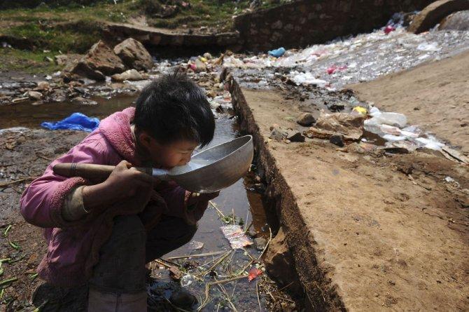 Questo bambino che beve l'acqua inquinata di un torrente