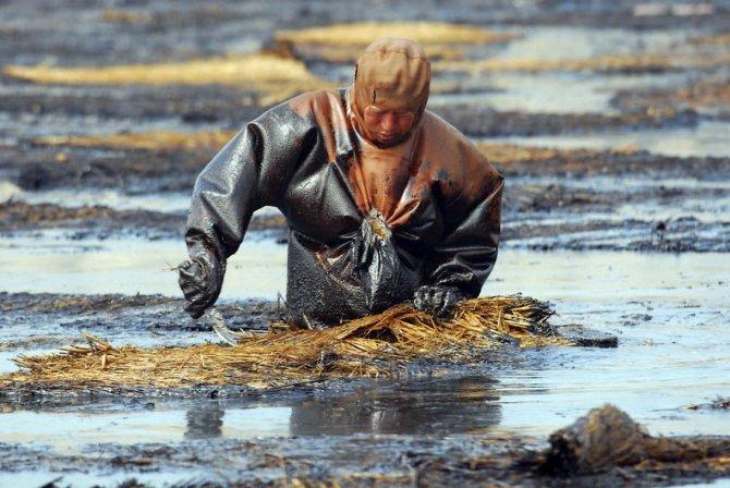 Quest'uomo che tenta di ripulire l'acqua dalle perdite di petrolio