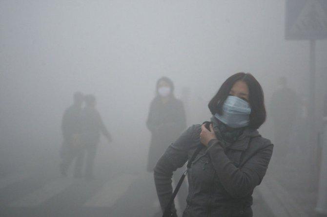 Questa ragazza che cammina attraverso una coltre di smog a Pechino