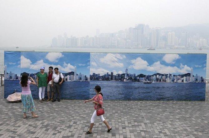 Questi turisti che a Hong Kong si fanno le foto davanti ad una falsa skyline, perché il vero panorama è così inquinato da non far vedere niente