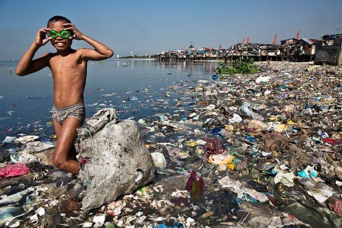 Questo ragazzino che cerca nel mare residui di plastica riciclabile da poter vendere a 35 cent al chilo per aiutare la sua famiglia