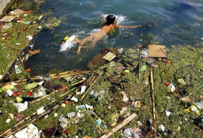 Questi bambini che nuotano nelle acque sporche e piene di alghe